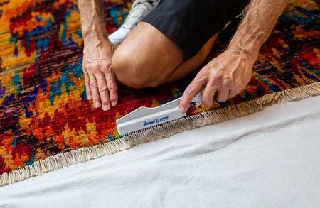 Technician grooming fringe on fine area rug