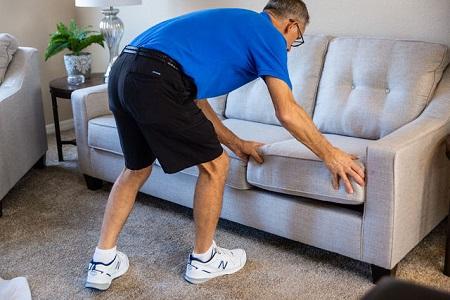 Technician replacing clean sofa cushions
