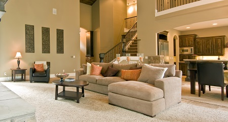 Furnished living room with carpet, upholstered sectional, kitchen in the background, and staircase to 2nd floor          r