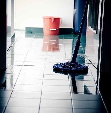 Partially wet tile floor with a mop and a bucket