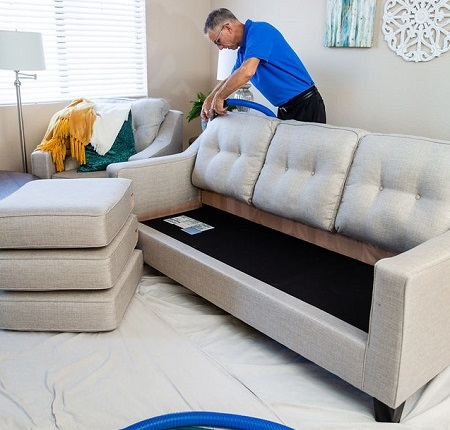 Technician cleaning a white sofa